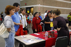 parents and students talking with college representatives
