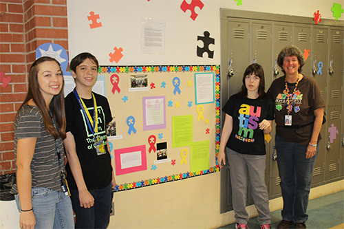Palo Verde paraprofessionals stand with students who participated in decorating the hallways.