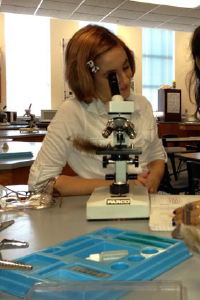 Female student looking at microscope