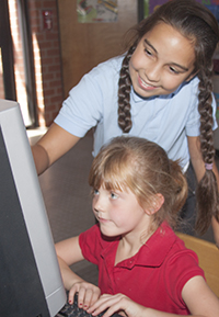 two girls looking at computer monitor