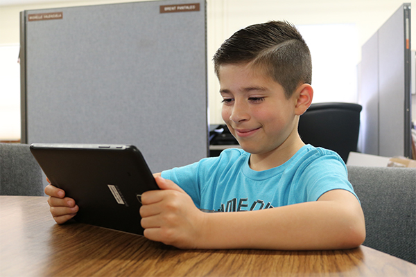 A young studet smiles as he learns on a tablet